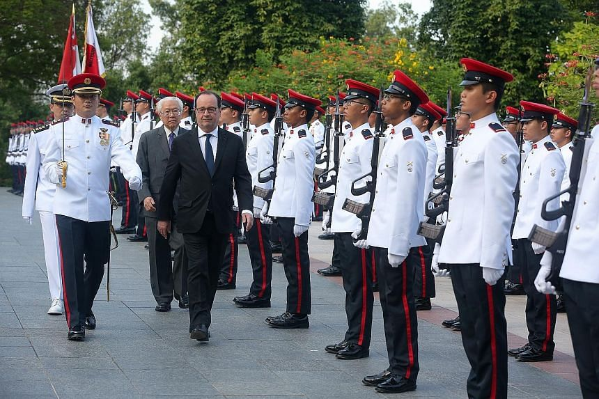 French President Francois Hollande inspecting the guard of honour with President Tony Tan Keng Yam at a welcome ceremony at the Istana yesterday. Mr Hollande is the first sitting French president to visit Singapore. Dr Tan and Mr Hollande at a state