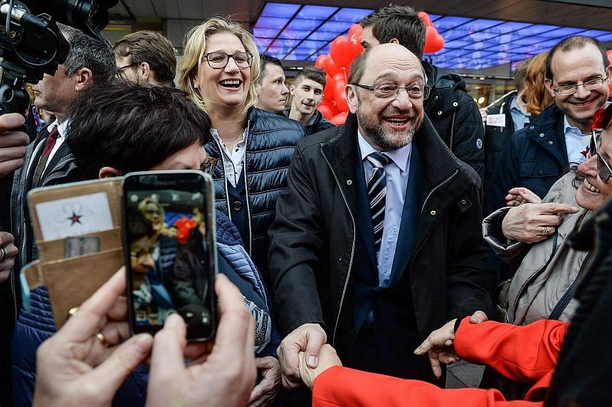 Mr Martin Schulz and his fellow Social Democrats on the campaign trail in Saarland last week, ahead of yesterday's vote in the small German state. The new leader has re-energised the centre-left party with a promise to tackle inequality, a pledge tha