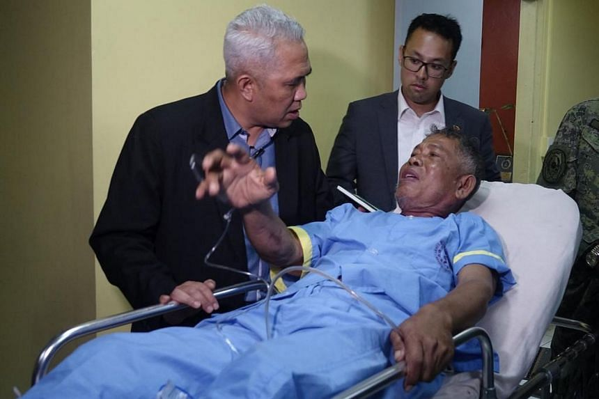Rescued Malaysian hostage Abdurahim Bin Sumas (right) talks with Malaysian Colonel Fazly Said (left), head of the Malaysian International Monitoring Team (IMT), inside the military headquarters in Zamboanga City.
