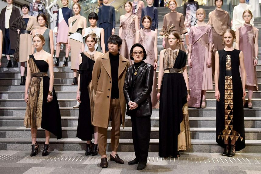 Japanese designers Yu Amatsu (centre, left) and Hanae Mori (centre, right) posing for photographers with their models after their 2017 Autumn/Winter Collection show of the Tokyo Fashion Week in Tokyo, on March 23, 2017.