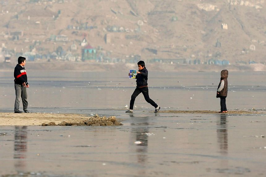 Afghan children play on a frozen lake in Kabul, Afghanistan, on Jan 9, 2017.
