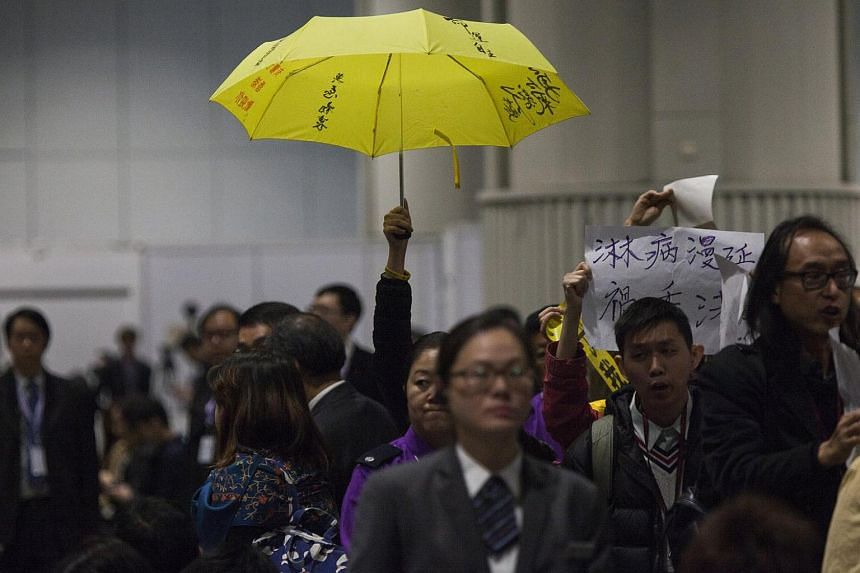 A pan-democratic election committee member holds a yellow umbrella, a symbol of the pro-democracy Occupy Central and Umbrella Movement of 2014, during the announcement of the result of the Hong Kong Chief Executive election in Hong Kong on Sunday, Ma