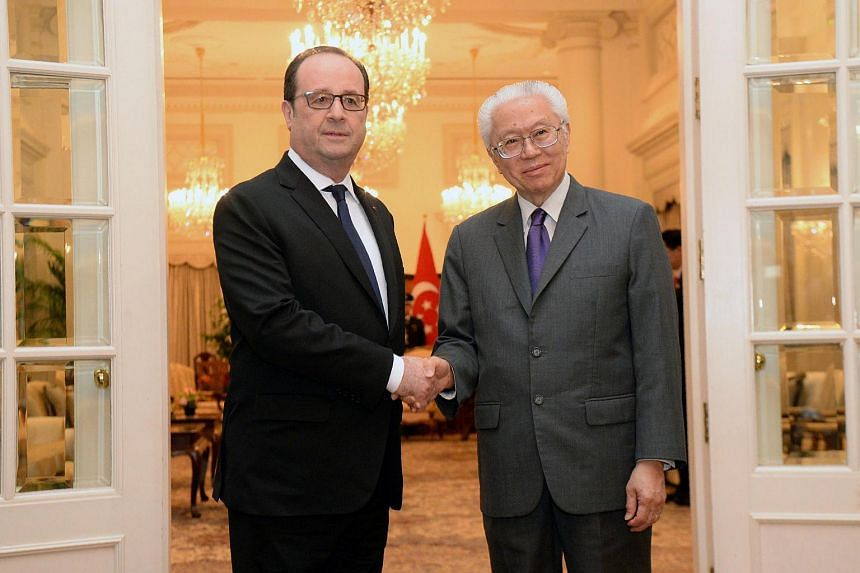 French President Francois Hollande (left) shakes hands with Singapore President Tony Tan Keng Yam after a welcoming ceremony at the Istana presidential palace.
