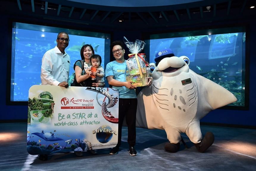 Mr Jagdesh Kumar, vice-president for attractions at Resorts World Sentosa, presenting the S.E.A. Aquarium annual pass and hamper, with Manta Ray mascot Mai, to Mr Samuel Ang, and his wife Claire, and their daughter Beatrice.