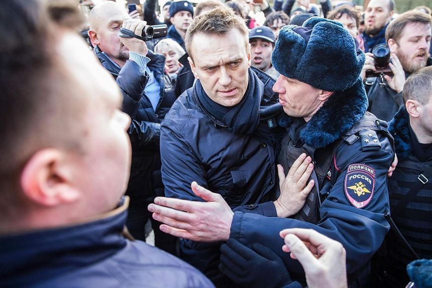 Police officers detaining Kremlin critic Alexei Navalny during an unauthorised anti-corruption rally in central Moscow.