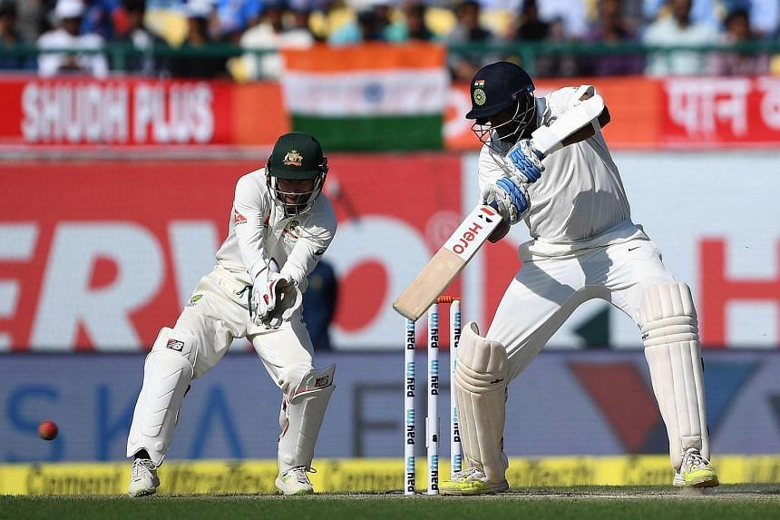 Australia's wicketkeeper Matthew Wade (left) watches as India's Ravichandran Ashwin plays a shot during their cricket match between India and Australia.