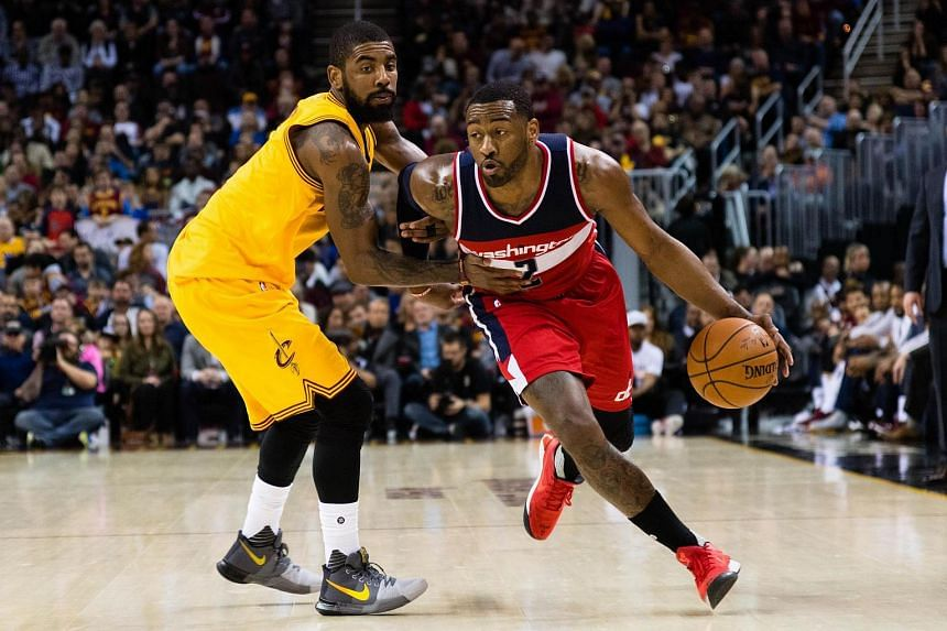 John Wall of the Washington Wizards drives past Cleveland Cavaliers' Kyrie Irving during the first half at Quicken Loans Arena.