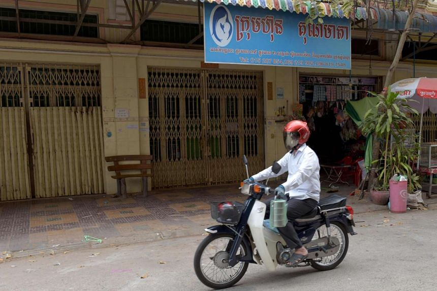 A man rides a motorbike past the offices of Ambrosia Labs in the Stung Meanchey neighborhood of Phnom Penh on March 16, 2017.