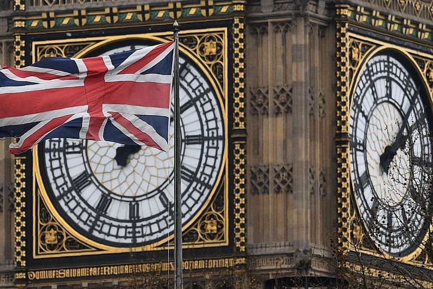 The Union Flag flying in front of the Great Clock of the Elizabeth Tower, at Britain's Houses of Parliament, in central London.