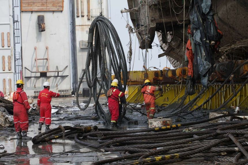 The salvage team working on the retrieved Sewol ferry on a semi-submersible transport vessel in the waters near Jindo, South Korea, on March 27, 2017.