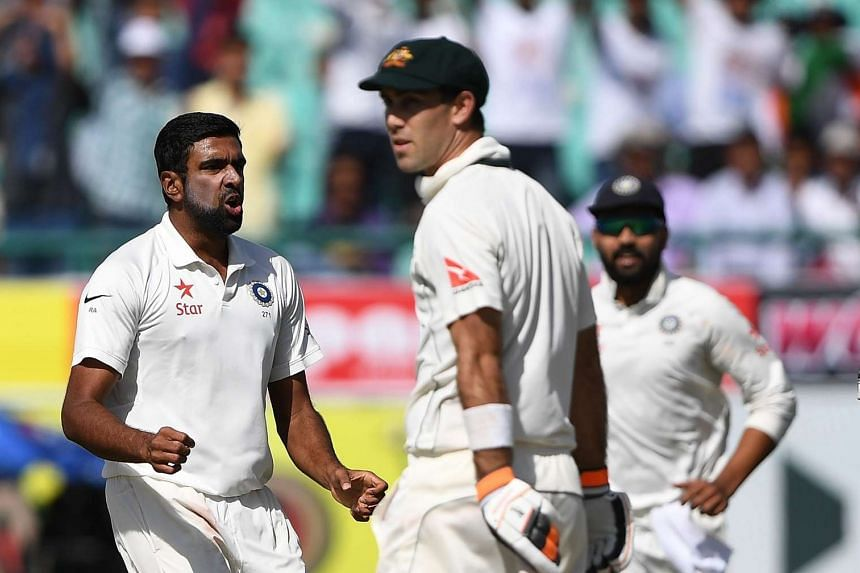 India's Ravichandran Ashwin (left) celebrating the wicket of Australia's Glenn Maxwell (center) during the third day of the fourth and last Test cricket match between India and Australia at The Himachal Pradesh Cricket Association Stadium in Dharamsa
