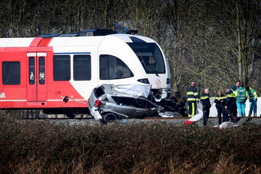Rescue workers operate at the scene of a train crash with a car, near Harlingen, the Netherlands, March 27, 2017.