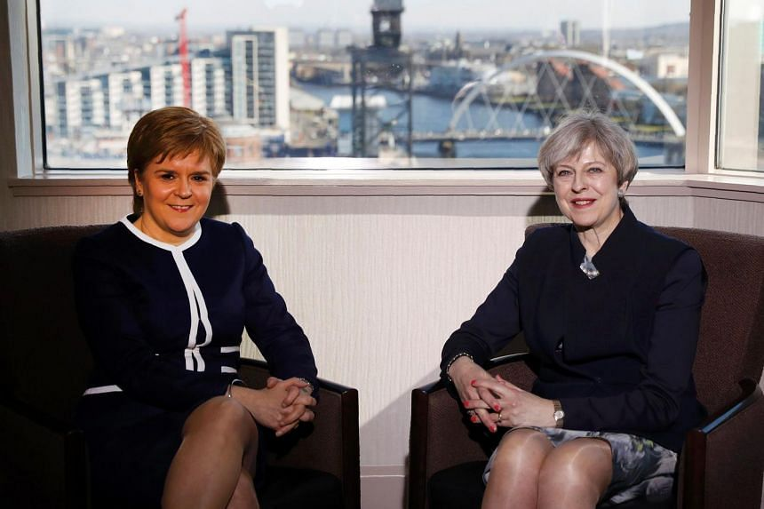 Britain's Prime Minister Theresa May (right) and Scotland's First Minister Nicola Sturgeon pose for a photograph ahead of their meeting in a hotel in Glasgow, Scotland, on March 27, 2017.