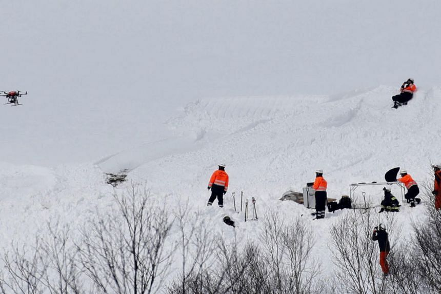 Firefighters and rescue workers using a drone investigate at the site of an avalanche in Nasu town, north of Tokyo, Japan, on March 28, 2017.