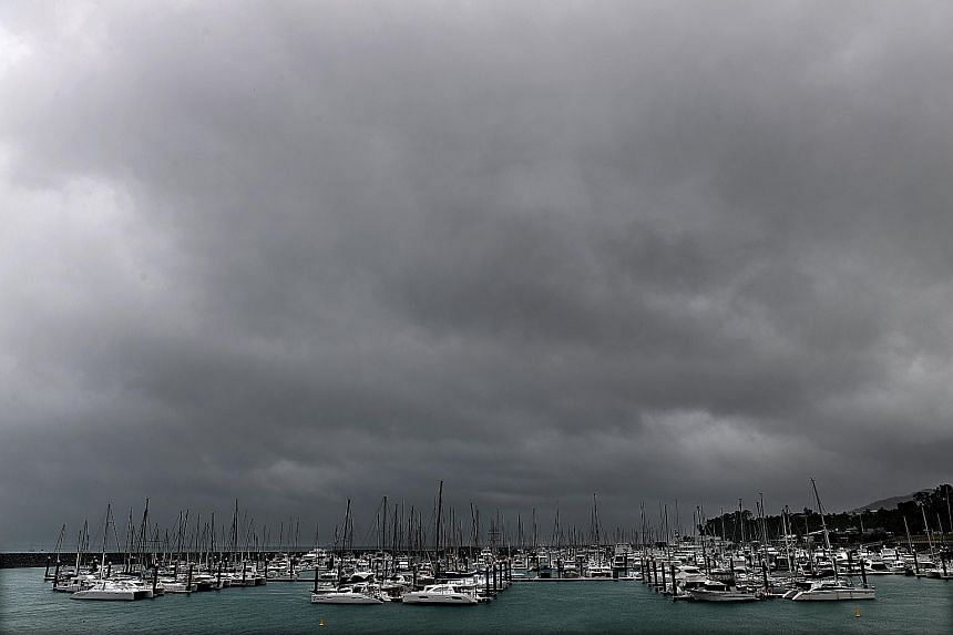 Dark clouds approaching Airlie Beach, Queensland, yesterday as residents in Townsville fill up sandbags in preparation for Cyclone Debbie. The powerful cyclone, packing destructive winds, is expected to hit land after daybreak this morning.