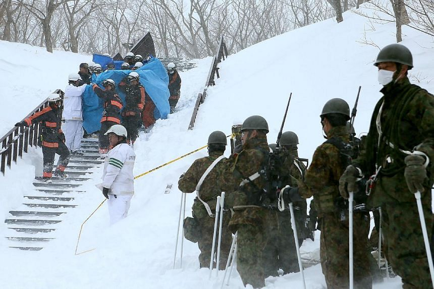 Firefighters carrying a survivor from the site of an avalanche in Nasu town, Tochigi prefecture, yesterday. Self Defence Force personnel were also present. Eight teenagers from a high school mountaineering club died, while dozens of other students an
