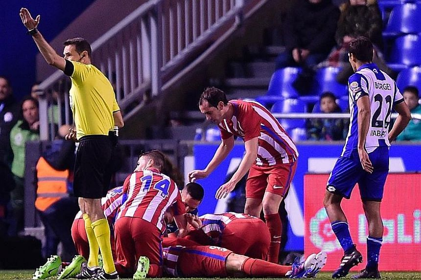"""Teammates surrounding striker Fernando Torres, who suffered """"traumatic brain injury"""" after a clash of heads on March 3."""