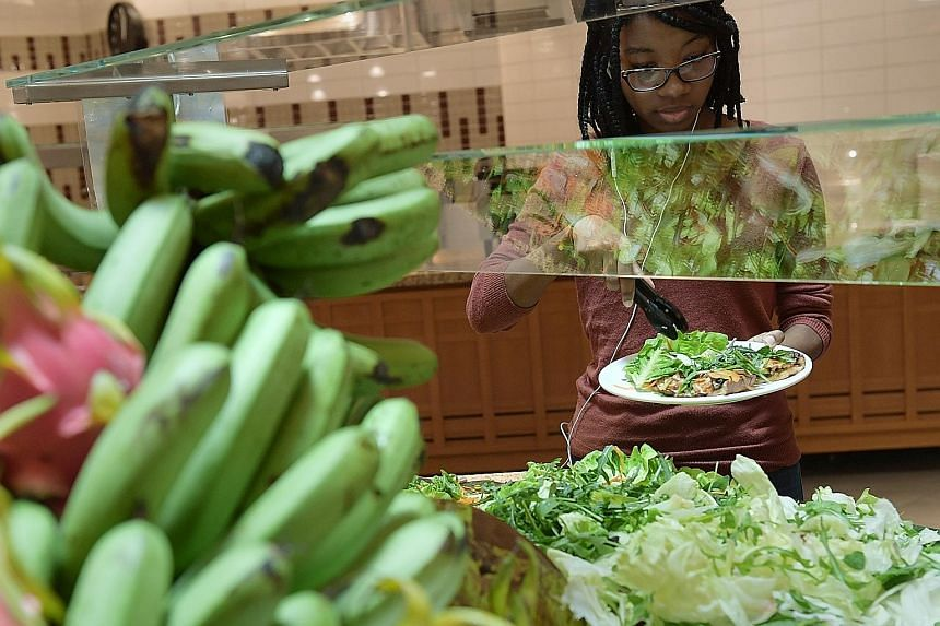 A student getting food from the salad bar at one of Yale-NUS campus' three dining halls, which have started serving fully vegetarian lunches once a week.