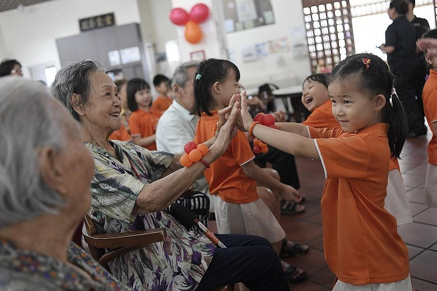 Children and seniors from the My First Skool and Silver Circle centres on the ground floor of Block 264 Serangoon Central playing games with one another yesterday.