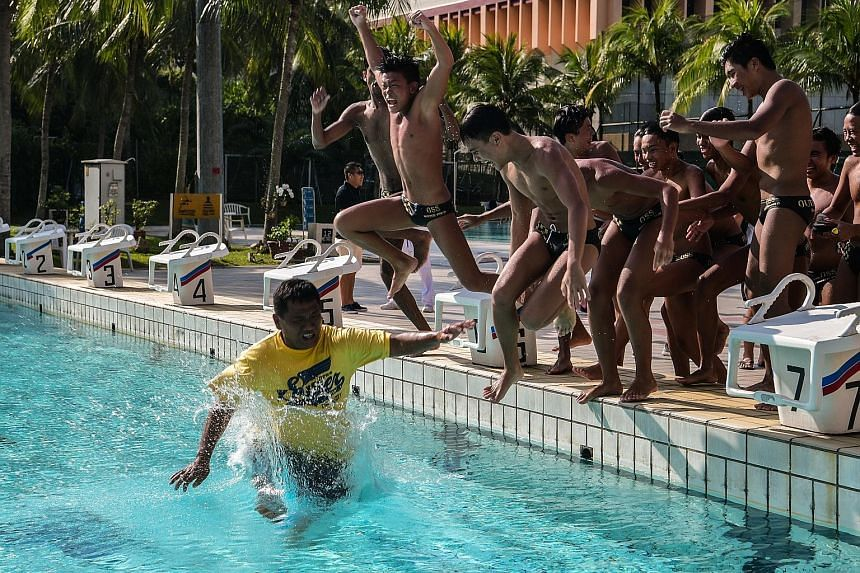 Outram Secondary's water polo boys jump in after pushing their coach Kuah Kar Huat into the pool while celebrating their win in the Schools National B Division boys' final yesterday. Zander Widjaja, Lum Jing Hao, Marc Chew, Ayers Fong and Keefe Law s