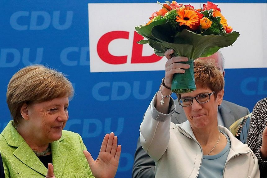 German Chancellor Angela Merkel, who leads the Christian Democrats, applauding the victorious state governor, Ms Annegret Kramp-Karrenbauer, at a party meeting yesterday.