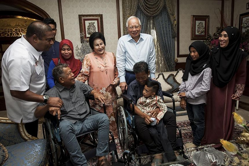 Sailors Abd Rahim Summas and Tayudin Anjut (holding child) and their families meeting Malaysian Prime Minister Najib Razak and his wife Rosmah Mansor at the Premier's residence yesterday. They were held by the Abu Sayyaf for almost a year.