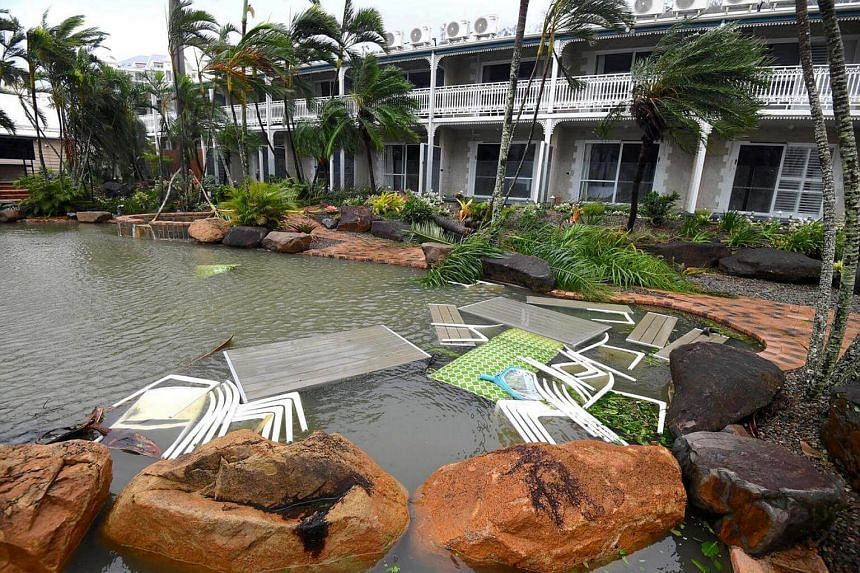 Outdoor furniture lies in a pool at a motel as Cyclone Debbie hits the northern Queensland town of Airlie Beach, located south of Townsville in Australia, on March 28, 2017.