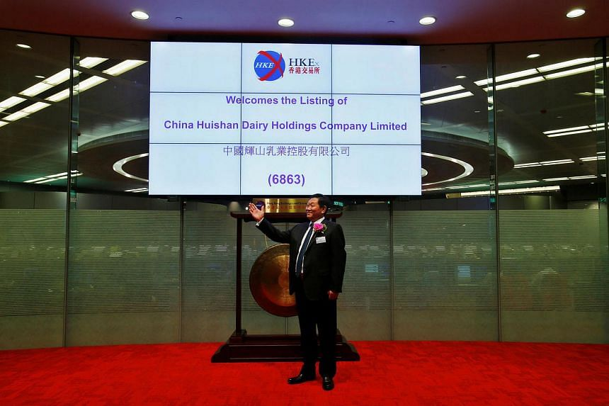 Yang Kai, chairman and CEO of China Huishan Dairy, takes part in a ceremony during the debut of the company at the Hong Kong Exchanges on Sept 27, 2013.