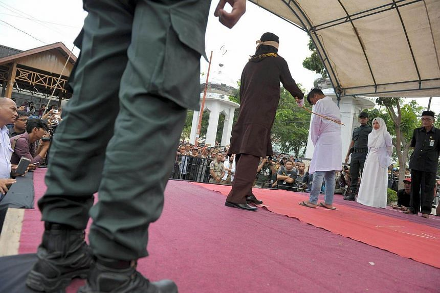 An Acehnese man getting whipped for spending time in close proximity with a woman who is not his wife, which is against Syariah law, in Aceh, on March 20, 2017.