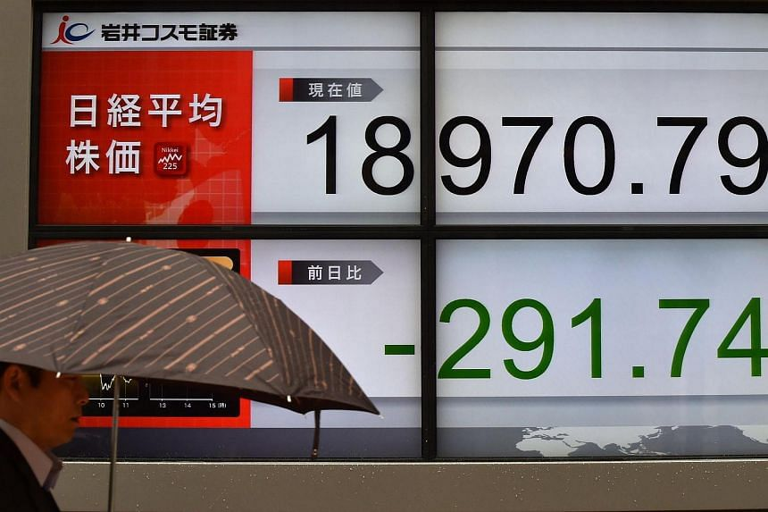 A pedestrian walking in front of an electric quotation board flashing the Nikkei key index of the Tokyo Stock Exchange in Tokyo, on March 27, 2017.
