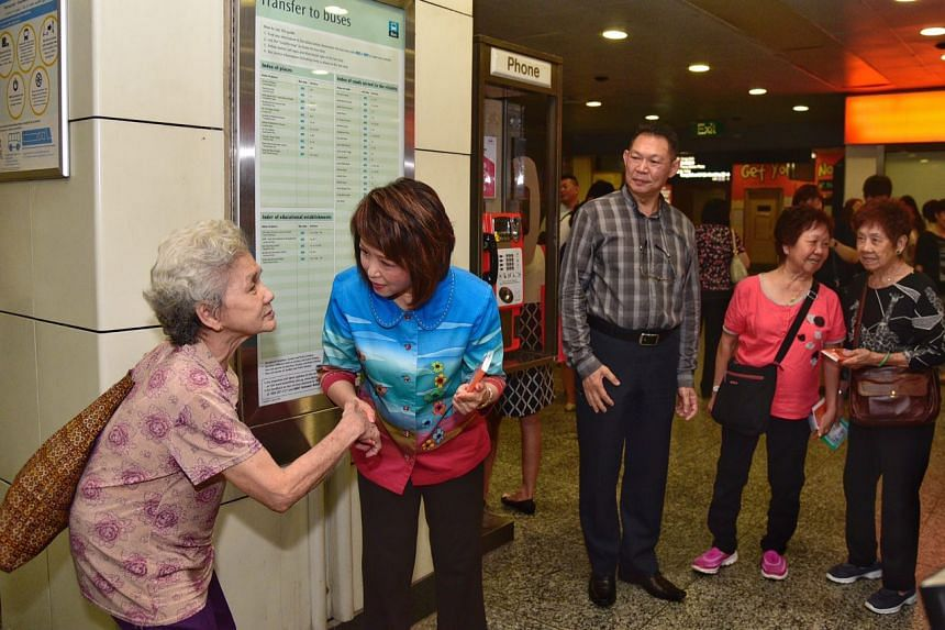 """Dr Lily Neo, MP for Jalan Besar GRC, distributes souvenirs consisting of a pack of tissue and an ez-link card holder with the message """"Seniors, Come Get A Lift, Make It A Safer Trip!"""" to an elderly woman on March 28, 2017."""