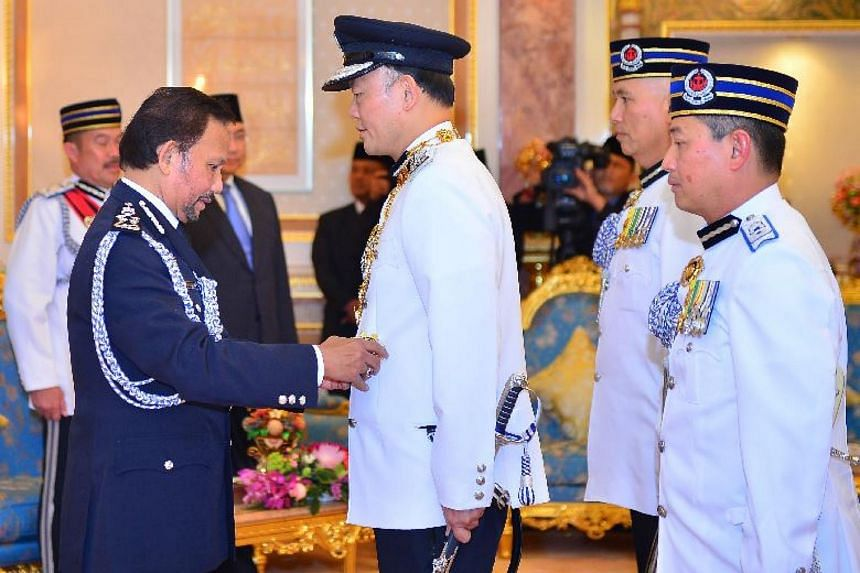Sultan of Brunei Hassanal Bolkiah presents Commissioner of Police Hoong Wee Teck with the state award.