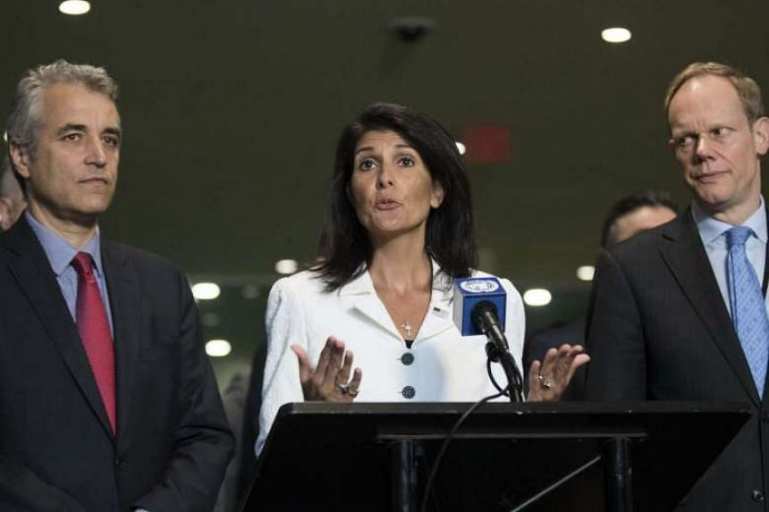 Flanked by French Deputy Representative to the UN Alexis Lamek (left) and Britain's Matthew Rycroft (right), Nikki Haley speaks to reporters at the UN headquarters.