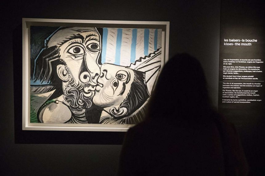 A visitor looks at the 'The Kiss' painting at the 'Picasso Primitif' exhibition in Paris on March 27, 2017.