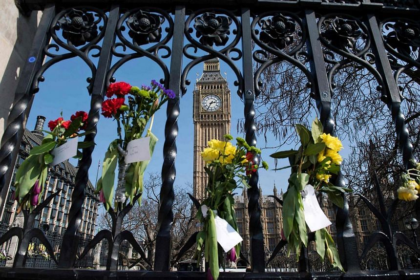 Floral tributes to the victims of the March 22 terror attack are seen on outside the Houses of Parliament in Westminster, central London, on March 27, 2017.
