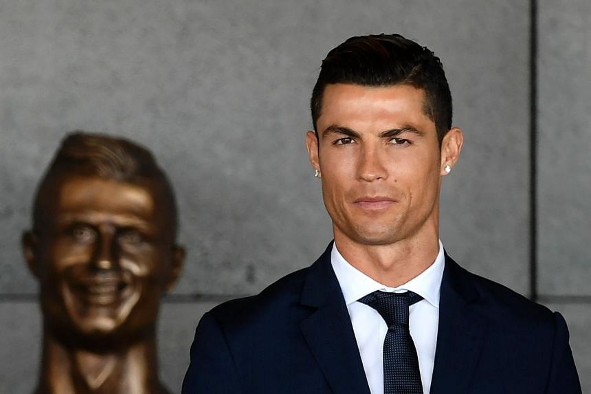 Ronaldo standing in front of the new statue of him at Madeira's airport in Funchal on March 29, 2017.