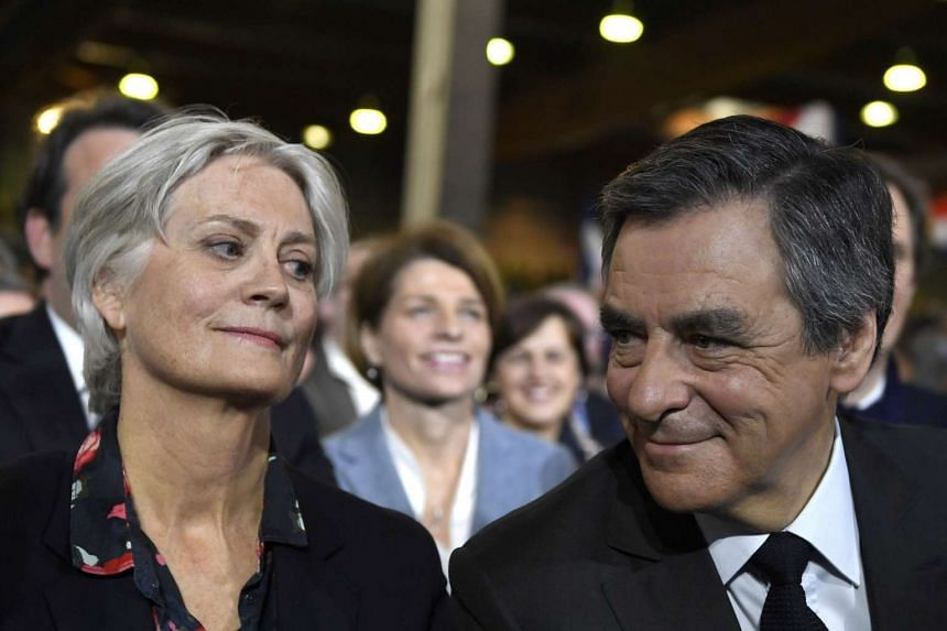 This file photo taken on Jan 29, 2017 in Paris shows French right wing candidate for the upcoming presidential election Francois Fillon (right) flanked by his wife Penelope (left), looking on during a campaign rally.