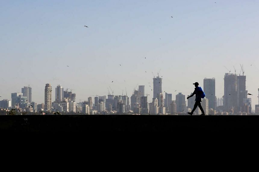 A man walking along a wall overlooking the central Mumbai's financial district skyline, India.