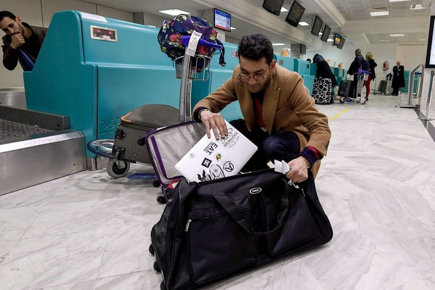 A Libyan traveller packs his laptop in his suitcase before boarding his flight for London at Tunis-Carthage International Airport on March 25, 2017.