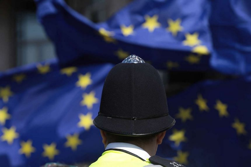 A police officer watches as protesters wave EU flags during an anti-Brexit protest in London, March 25, 2017.