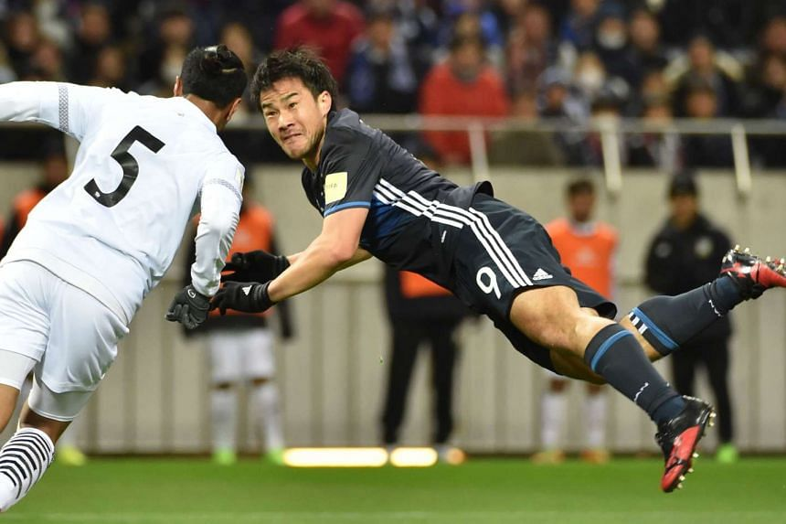 Japan's forward Shinji Okazaki (right) follows his scoring shot past Thailand's Adison Promrak (left) during the group B World Cup 2018 qualifying football match between Japan and Thailand, on March 28, 2017.
