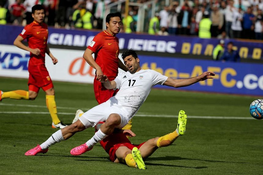 Iran's Mehdi Taremi (left) plays against China's Zhang Linpeng during the 2018 World Cup qualifying football match between Iran and China at the Azadi Stadium in Tehran on March 28, 2017.