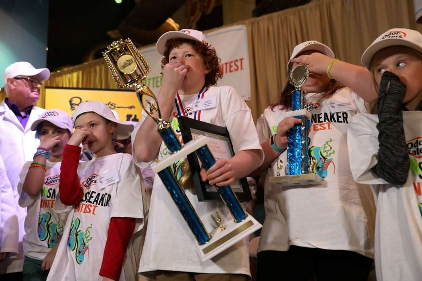 Connor Slocombe, from Eagle River, Alaska, holds his trophy with other contestants after winning Odor-Eater's Rotten Sneaker Contest at Ripley's Believe It or Not! in Times Square in New York.