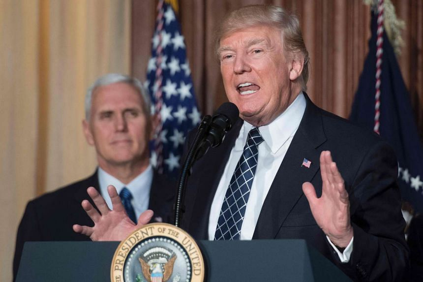 US President Donald Trump speaks (centre) before signing the Energy Independence Executive Order at the Environmental Protection Agency Headquarters in Washington, DC, on March 28, 2017, with Vice-President Mike Pence (left).
