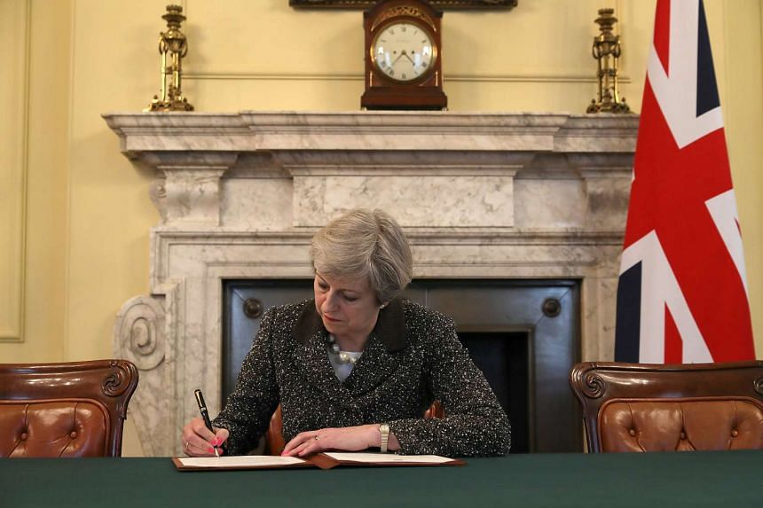 British Prime Minister Theresa May in the cabinet office signs the official letter to European Council President Donald Tusk invoking Article 50 and the United Kingdom's intention to leave the EU on March 28, 2017 in London, England.