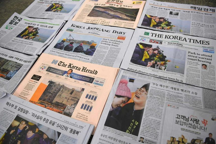 South Korean newspapers carry, on March 29, 2017, front-page stories about bone fragments found from the sunken Sewol ferry and pictures of relatives of the missing people from the ferry disaster.