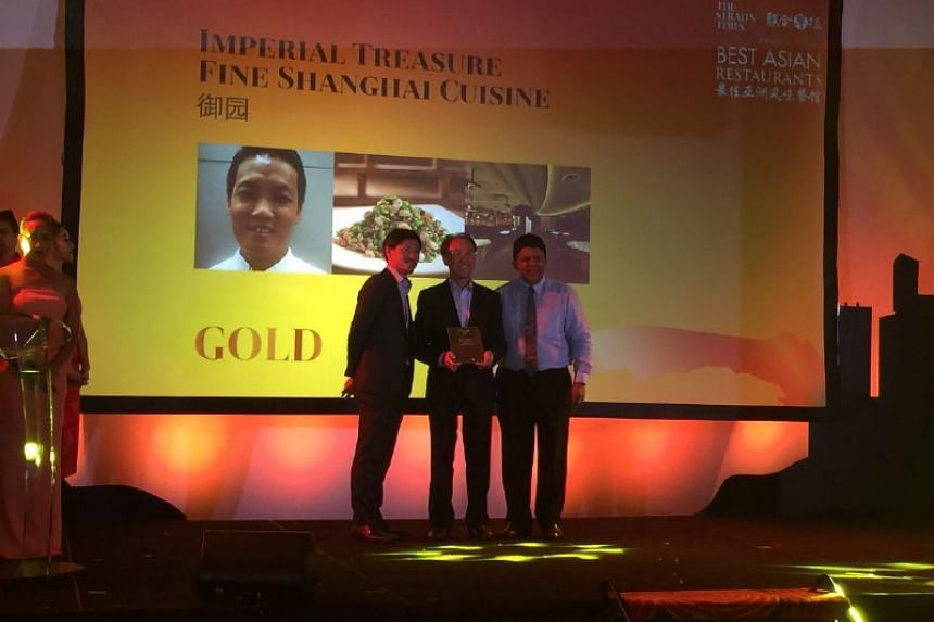 Vincent Leung, who oversees group operations for the Imperial Treasure Restaurant Group, receives the Gold award for the group's Imperial Treasure Shanghai Cuisine restaurant at the Best Asian Restaurants Awards on March 29, 2017, with SPH deputy chi