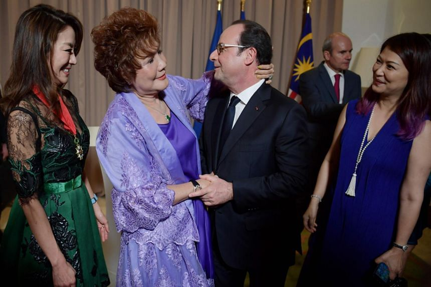 Mr Hollande speaks to Yeoh and her mother (second from left) after conferring the Legion d'Honneur award to Yeoh.