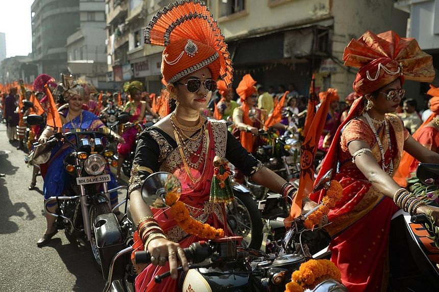 Indian women dressed in traditional attire riding motorcycles in a procession celebrating Gudi Padwa, or the Maharashtrian New Year, in Mumbai yesterday. Gudi Padwa is the Hindu New Year for people in India's Maharashtra state and marks the end of a