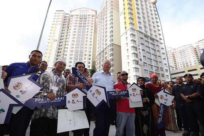 Prime Minister Najib Razak with new owners of flats in Putrajaya built under the civil service housing scheme PPA1M. He handed over 1,680 keys to the homes on Monday.